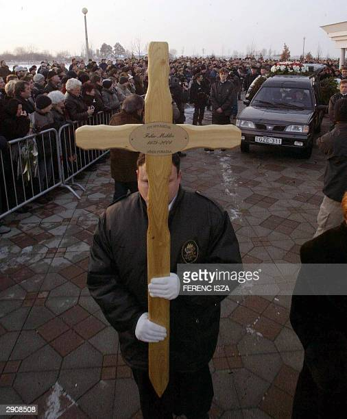 A man carrying a cross leads the funeral procession for Hungarian soccer player Miklos Feher 28 January 2004 in Gyor 120 km east from Budapest The...