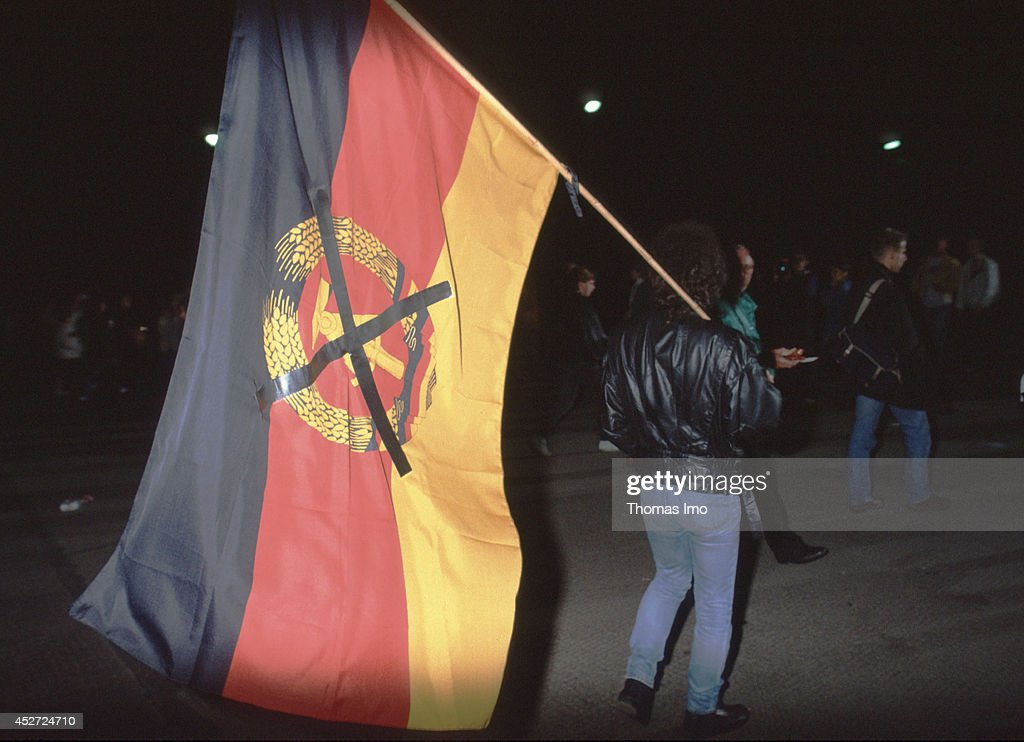 Man carrying a crossed flag of the German Democratic Republic on German Unity Day on October 03, 2014, in Berlin, Germany. The year 1990 marks the 25th anniversary of the fall of the Berlin Wall.