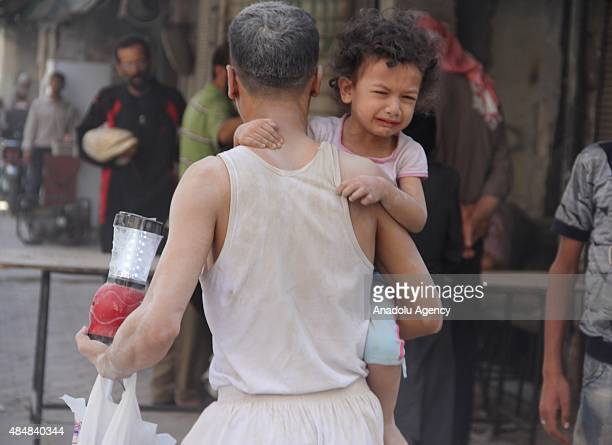 A man carrying a crying child and some belongings is taking them to a safe zone following Assad forces barrel bomb attack to Qadi Askar neighborhood...