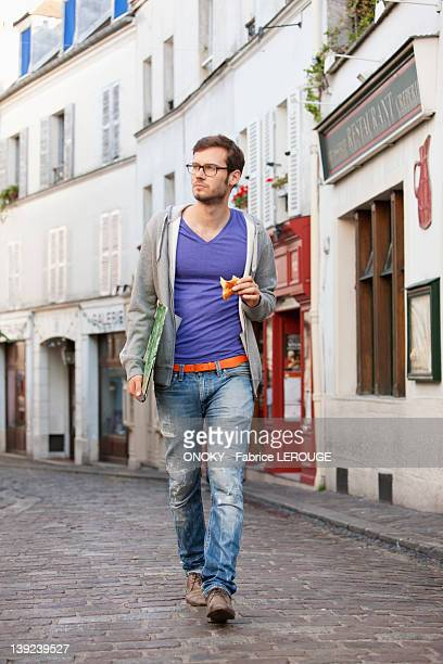 Man carrying a file while eating food, Paris, Ile-de-France, France
