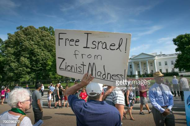 A man carrying a Free Israel From Zionist Madness sign protests in front of The White House on June 4 2017 in Washington DC The nation's capital the...