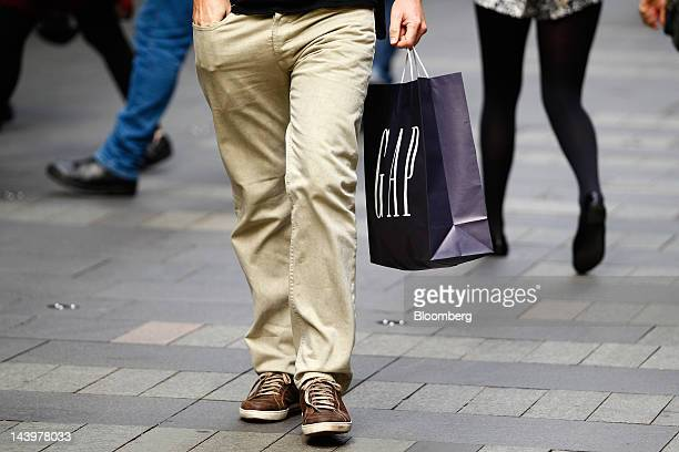 A man carrying a Gap Inc shopping bag walks along the Pitt Street shopping mall in Sydney Australia on Saturday May 5 2012 The Australian government...