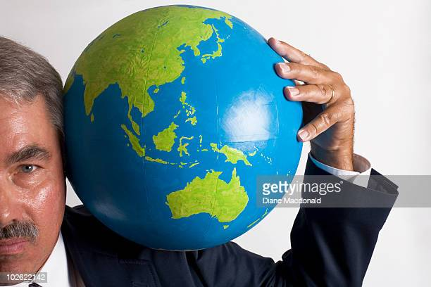 A man carrying a globe on his shoulders