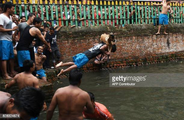 A man carrying a goat jumps into a pond during an ancient annual Hindu festival ritual in Khokana village on the outskirts of Kathmandu on August 9...