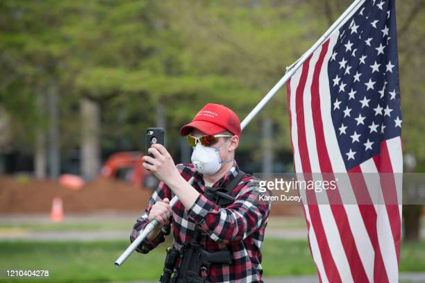 A man carrying a gun and a flag and wearing a Make America Great Again hat and a protective mask gathers with others at a 'Hazardous Liberty Defend...