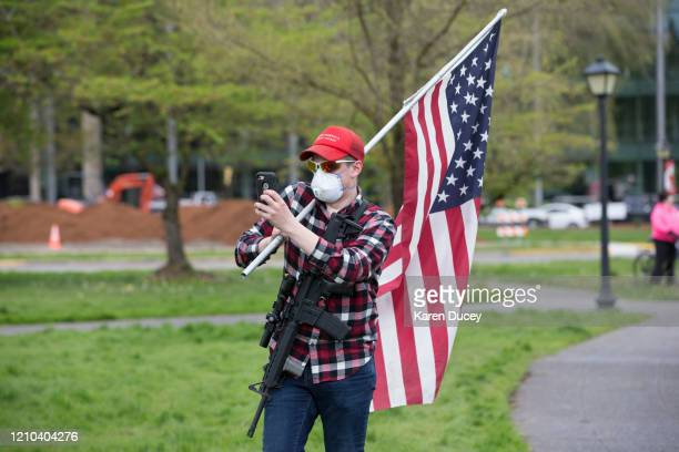 A man carrying a gun and wearing a Make America Great Again hat and a mask gathers with others at a 'Hazardous Liberty Defend the Constitution' rally...