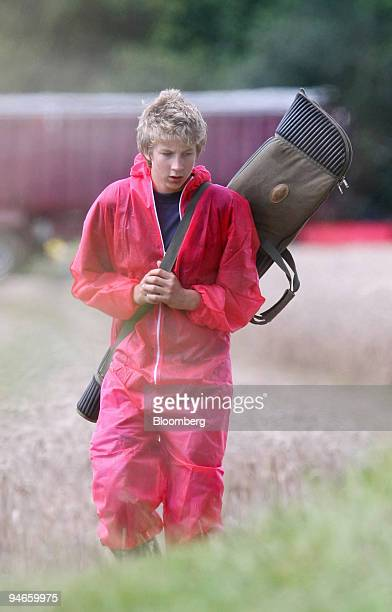 Man carrying a gun bag leaves after a cull of infected cattle on the second farm to confirm an outbreak of foot-and-mouth in the village of Normandy,...