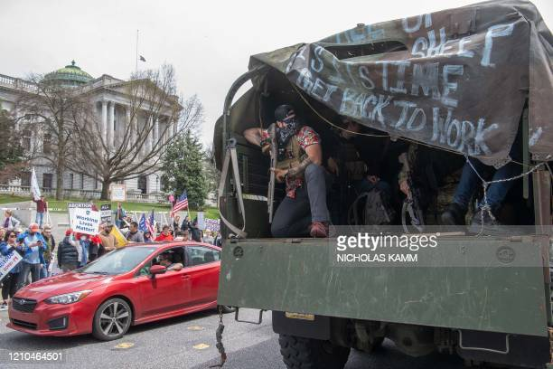 """Man carrying a gun takes part in a """"reopen"""" Pennsylvania demonstration on April 20, 2020 in Harrisburg, Pennsylvania. - Hundreds of people including..."""