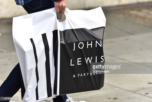 A man carrying a John Lewis and Partners shopping bag at Oxford Street in London John Lewis has posted losses of £259m for the first half of the year...