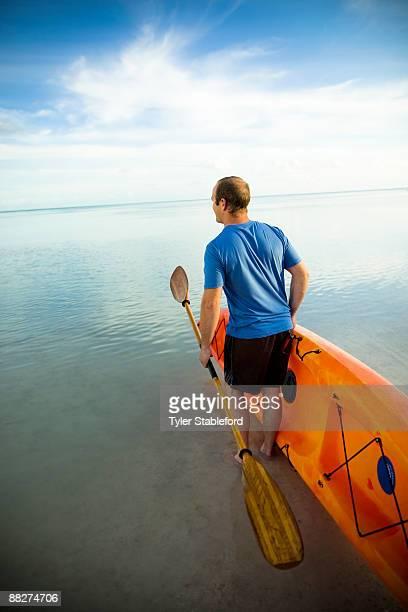 A man carrying a kayak into the ocean.