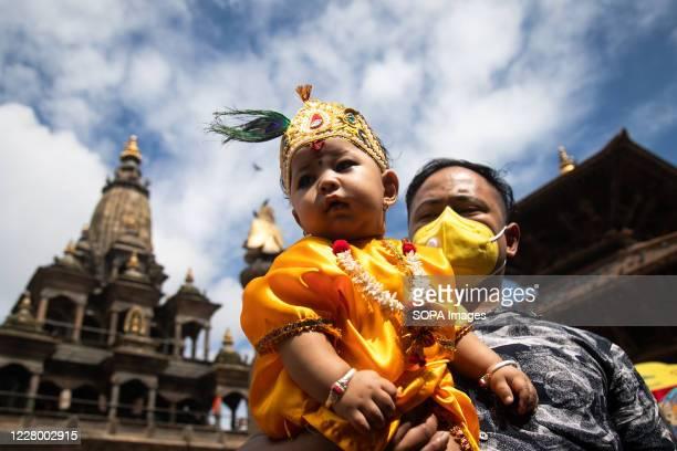 A man carrying a kid dressed as Lord Krishna during the festival at Krishna Mandir Krishna Janmashtami is an annual Hindu festival that celebrates...