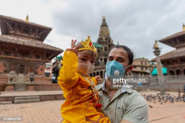 A man carrying a kid dressed as Lord Krishna wearing face masks during the festival at Hanuman Dhoka Sadak near Kathmandu Durbar Square Krishna...