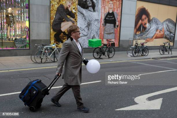 A man carrying a lighting fixture attached to his hand crosses the road on 22nd November 2017 in London England