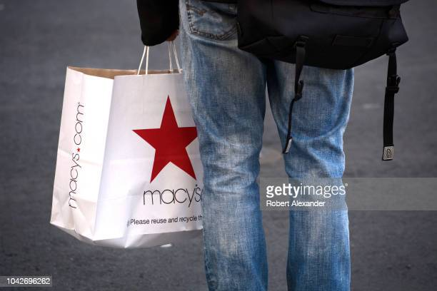 SAN FRANCISCO CALIFORNIA SEPTEMBER 13 2018 A man carrying a Macy's department store shopping bag waits at an intersection in San Francisco California