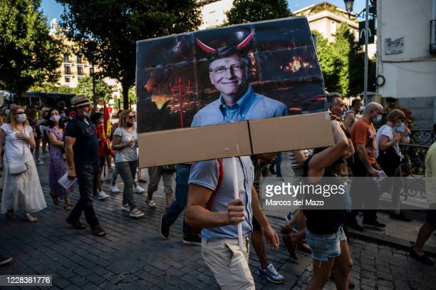 Man carrying a picture of Bill Gates protesting during a demonstration against the mandatory use of face masks, the use of a vaccine against...
