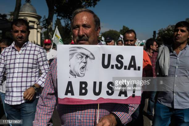 A man carrying a placard that reads 'USA abuses' with the face of Donald Trump during a demonstration Olive oil producers march to the Agriculture...