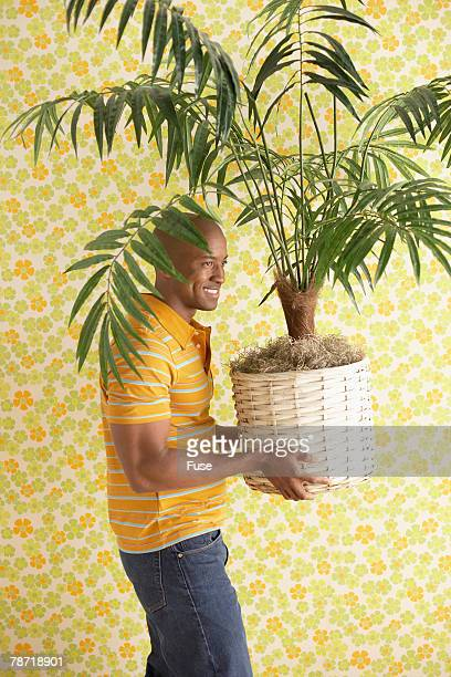 Man Carrying a Potted Plant