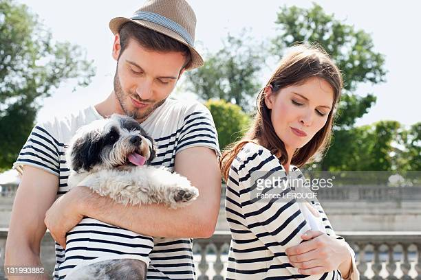 man carrying a puppy and smiling with a woman looking sad, paris, ile-de-france, france - um animal - fotografias e filmes do acervo
