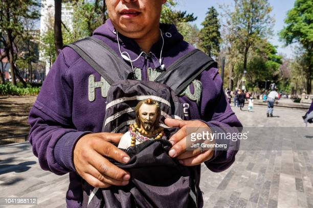 A man carrying a religious statue in a bag in Alameda Central