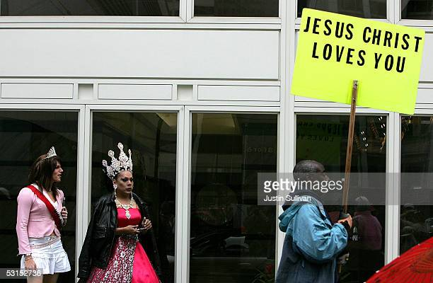 Man carrying a religous sign walks by two men dressed as woman before the start of the 2005 San Francisco Pride Parade June 26, 2005 in San...