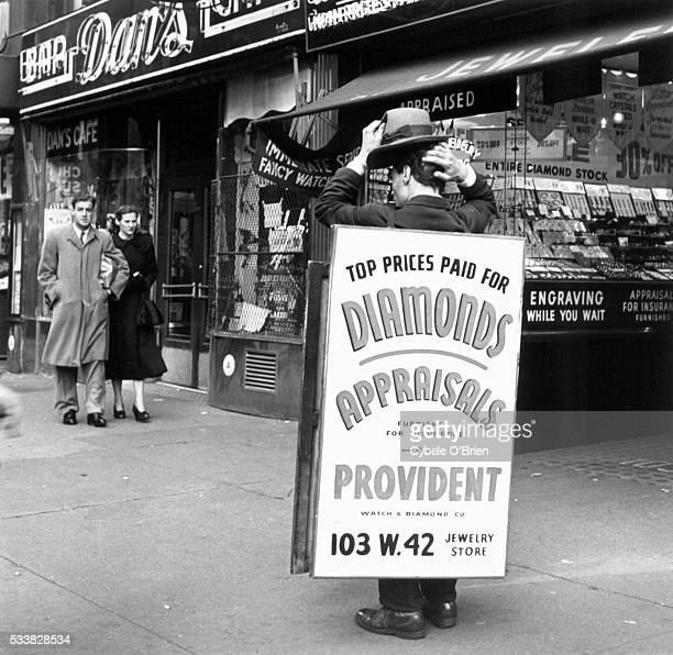 A man carrying a sandwich board scratches his head in front of the diamond store for which he advertises