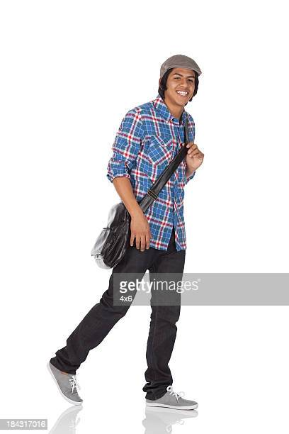 Man carrying a shoulder bag and smiling