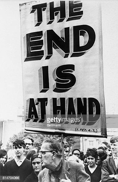 """Man carrying a sign reading """"The End Is At Hand"""" rants to spectators at Speakers Corner in Hyde Park, London. 