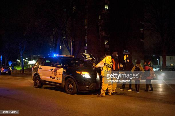A man carrying a sign that reads 'BLACK LIVES MATTER' confronts a police vehicle as protestors marched from the 4th Precinct Police Station to a...