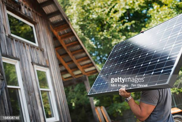 a man carrying a solar panel on a green construction site, working on a green building project. - solar panels stock photos and pictures