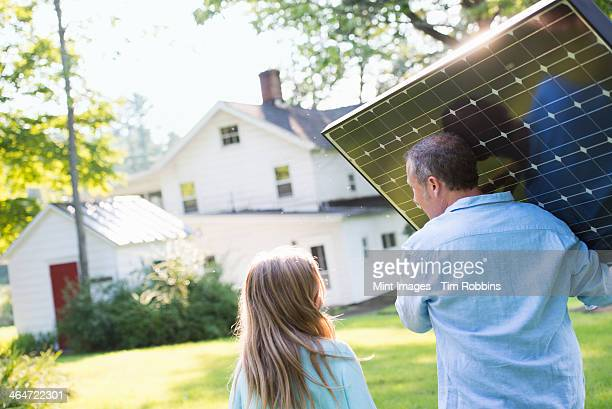 a man carrying a solar panel towards a building under construction. - solar equipment stock pictures, royalty-free photos & images