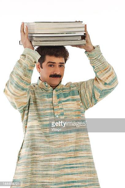 man carrying a stack of books on his head - man holding book stock pictures, royalty-free photos & images