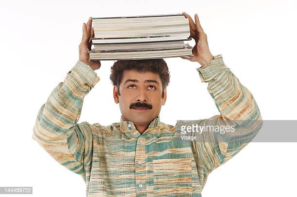 Man carrying a stack of books on his head