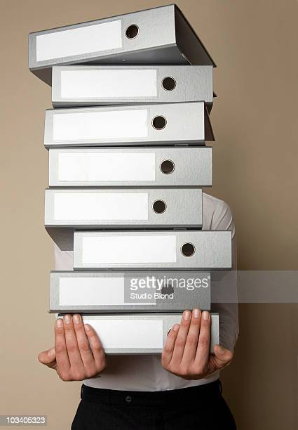 A man carrying a stack of folders