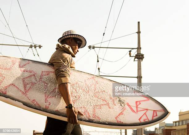 Man carrying a surfboard, Cape Town, Western Cape Province, South Africa