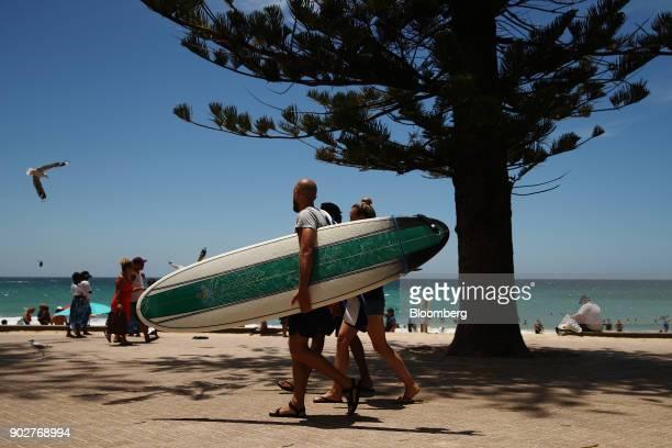 A man carrying a surfboard walks along the promenade at Manly Beach in Sydney Australia on Friday Jan 5 2018 The Australian Bureau of Statistics is...