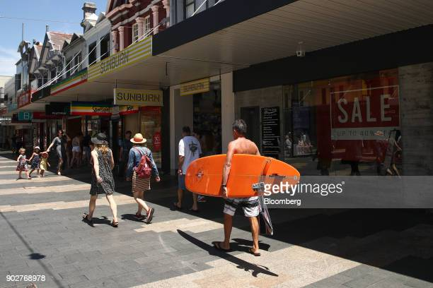 A man carrying a surfboard walks past stores in the Manly Corso retail area in Sydney Australia on Friday Jan 5 2018 The Australian Bureau of...