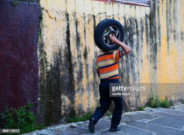 a man carrying a tire - somente adultos - fotografias e filmes do acervo