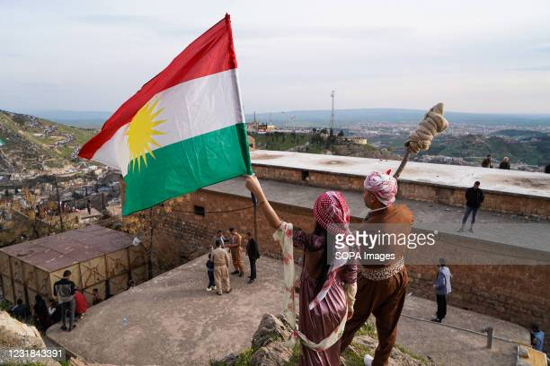 Man carrying a torches stands with a girl carrying the Kurdistan flag next to a church during the Nowruz celebration. The town of Akre in the Duhok...