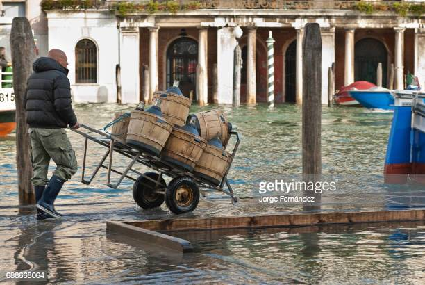 Man carrying a trolley full of winw containers on a street flooded by 'acqua alta'