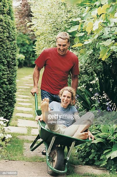 Man Carrying a Woman in a Wheelbarrow on a Garden Path