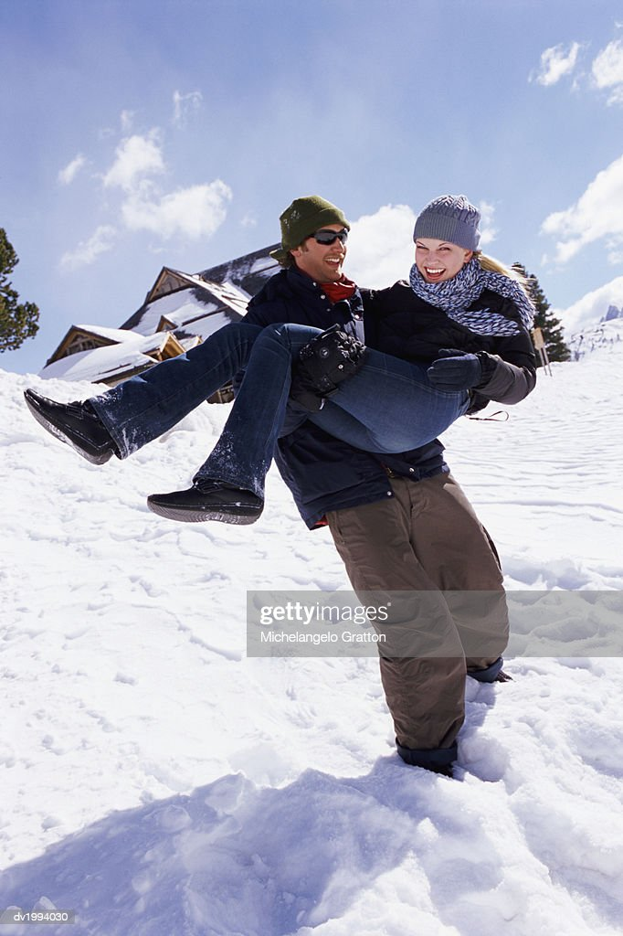 Man Carrying a Woman in His Arms in the Snow : Stock Photo