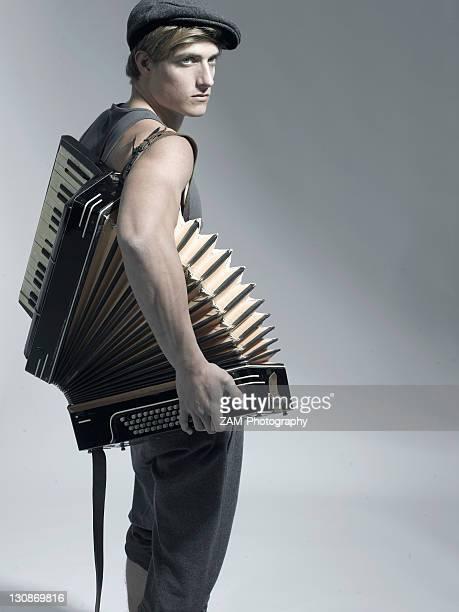 Man carrying an accordion, fashion shoot