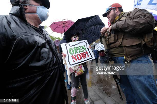 A man carrying an assault rifle stands near a protester holding a banner reading Open Now at the ReOpen Oregon Rally on May 2 2020 in Salem Oregon...