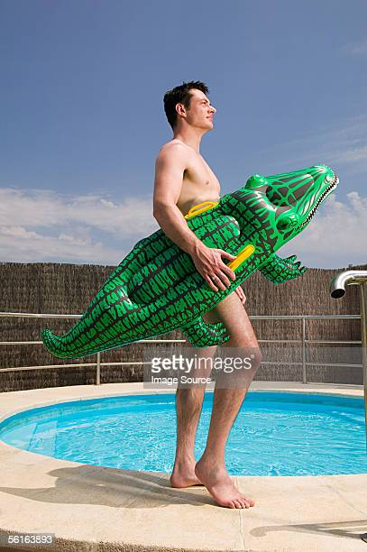 Man carrying an inflatable crocodile