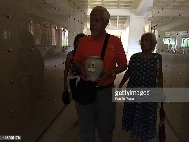 A man carrying an urn containing the creamted body of his father The urn will be placed at the vault inside San Ezekiel Moreno columbarium in Las...