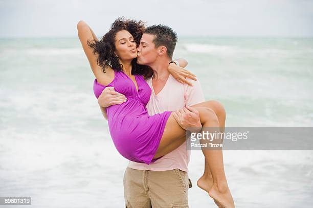 man carrying and kissing a woman on the beach - casal heterossexual - fotografias e filmes do acervo