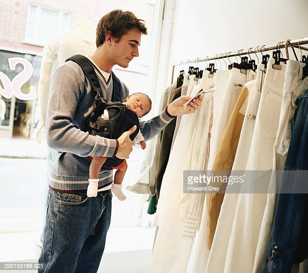 Man carrying baby girl (3-9 months), looking at price tag in shop