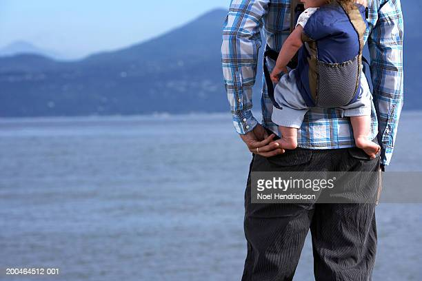 Man carrying baby (6-9 months) on back, standing on beach, rear view