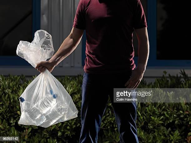 man carrying bag of water bottles