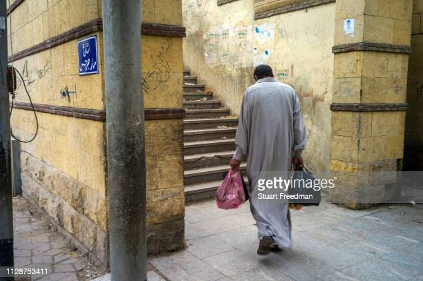 Man carrying bags of shopping walks towards steps on a Cairo street.